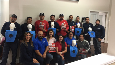 An image of the Made in the Shade crew gathered together and standing with CPR dummies