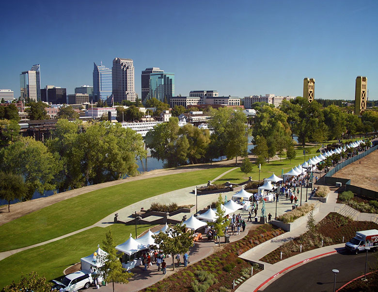 An arial photo of an outdoor festival in Sacramento with lots of people and white tents along the river side.