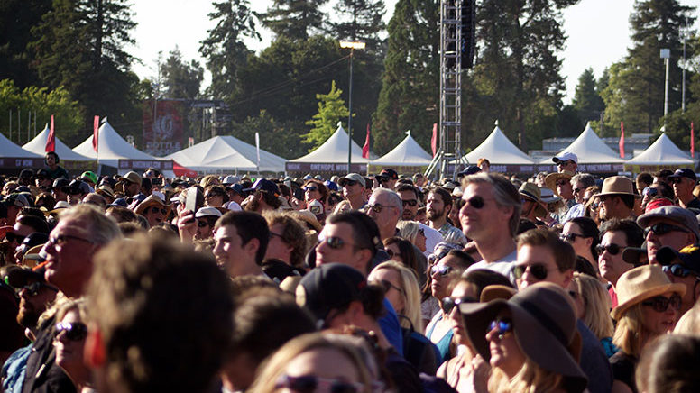 a photo of a large crowd at an outdoor concert event with Made in the Shade tents in the background lining the skyline