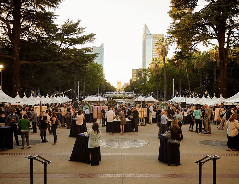 An image of the Capital Wine Festival with white tents throughout and lots of people mingling and drinking wine
