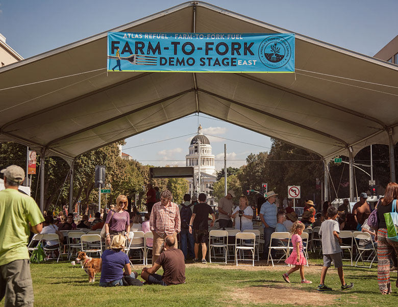 An image of a large Made in the Shade tent with people visiting with each other in front of it, and the Capitol Building behind it. A sign on the front of the tent reads 'Farm to Fork Demo Stage East'.